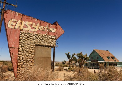 LANCASTER, CALIFORNIA, USA - AUGUST 2016 : Abandoned 50's motel along a desert California road on a hot summer day. Old motel sign and Joshua trees on the composition.