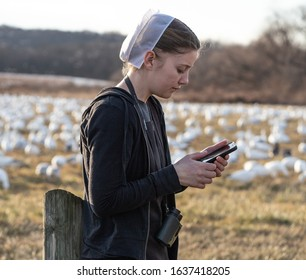 Lancaster County, Pennsylvania, USA: February 3, 2020: Young Amish women in black dress and white hair covering using cell phone