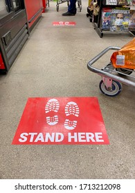 Lancaster Ohio/USA-April 2020: Stand Here decals or stickers on the floor at a store checkout lane to enforce social distancing