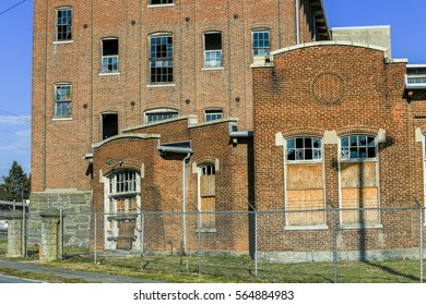 Lancaster, PA - January 25, 2017: An old, abandoned, and closed factory building is now in disrepair with broken windows and surrounded by a chain link fence with barb wire.