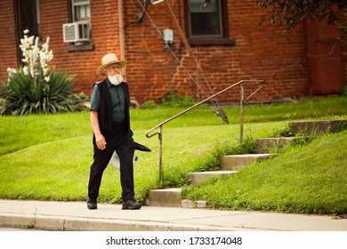 Lancaster, PA / USA - 7/4/2013: Old amish man walking on the street alone at day