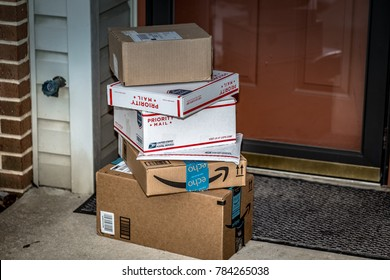 Lancaster, PA, USA - December 15, 2017: USPS Priority Mail boxes, Amazon, and other packages delivered at a residential home front door.