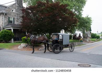 Lancaster, Pennsylvania/USA - May 29, 2018: Amish Farmer Rides House Drawn Buggy on Modern City Street