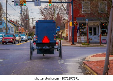 LANCASTER, USA - APRIL, 18, 2018: Outdoor view of the back of old fashioned Amish buggy with a horse riding on urban road surrounding with cars and traffic lights