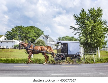 LANCASTER, USA - JULY 13, 2010: amish people ride in their horse carts in Lancaster, USA. Amish people don't use electricity as well as cars. They life the traditional way of the 17th century.