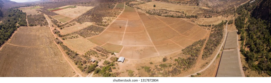 land from above agricultural farm with mountains and river birds eye view