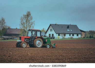Land being cultivated and prepared for sowing with a tractor. Crispy texture in the soil. Old russian tractor with modern sow machine attached. Wheel, gauges and cabin.