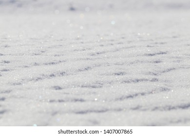 land covered with snow in the winter season. On a snowdrift, irregularities and lines are visible. In the sharpness there is a line in the center of the photo, close-up.