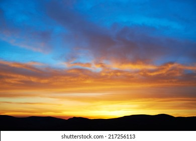 Land with and dramatic colorful sky at sunset