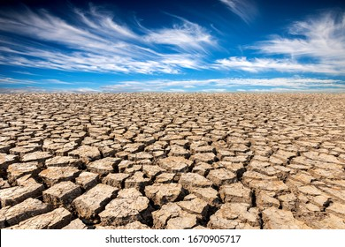 Land with dry and cracked ground and fluffy white clouds scatter in full light clear sky.Desert,Global warming background.