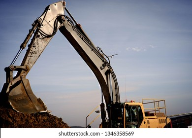 A land excavator in a construction site in the UK, with an arched arm.