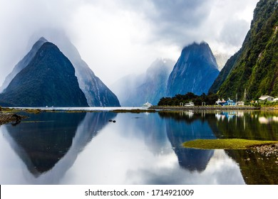 Land of hobbits - New Zealand. Port of tourist and pleasure ships, yachts and boats. Storm clouds cover the sky over the ocean fjord Milford Sound.  Concept of exotic, photographic tourism