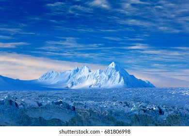 Land of ice. Travelling in Arctic Norway. White snowy mountain, blue glacier Svalbard, Norway. Iceberg in North pole. Blue sky with ice floe.