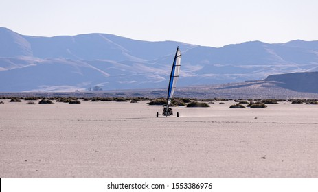 Land sailing in Alvord desert, Oregon. A blow cart surfing across playa,  Steens mountains in the background