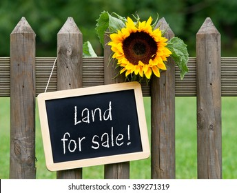 Land for sale - chalkboard with text and sunflower