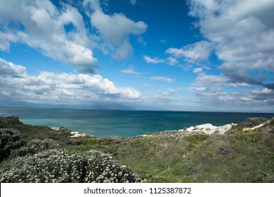 Land, sea & skies, coast line with rocky shore line and blue cloudy skies