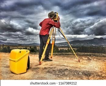 A land surveyor looking through a trimble robotic total station theodolite survey equipment.