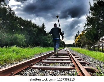 A land surveyor mapping a railway line with a trimble gps rover survey equipment