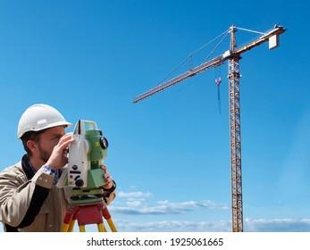Land surveyor works on geodetic total station