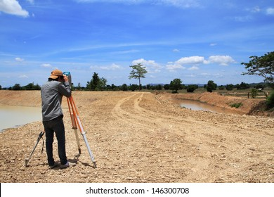 Land surveyors using camera on construction site