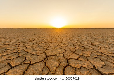 The land that is barren and cracked from the hot sun in the summer, with the bright light of the sun as the background
