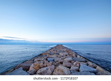 Landacape with rocky pier by the sea with cloudy horizon line and clear blue morning sky