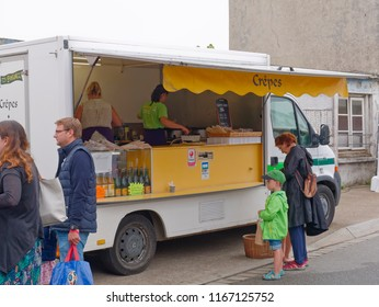 Landeda, France - August 14 2018: On a grey and damp morning at Landeda street market a lady and young child stand besides the hot crepes van.