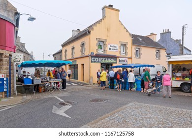 Landeda, France - August 14 2018: At the Landeda street market shoppers gather round the fish and haberdashery stalls.