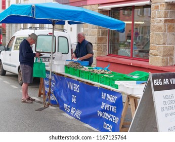 Landeda, France - August 14 2018: At the Landeda street market a man purchases shell fish from a stallholder.