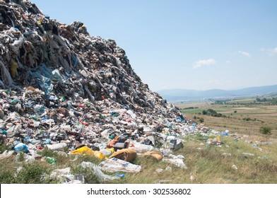 Landfill near crop fields. Enormous Trash wave near fields