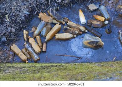 Landfill (plastic bottles) into the river. Environmental pollution.