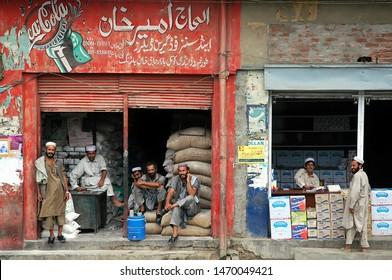 Landi Kotal, Khyber Pass, Khyber Pakhtunkhwa / Pakistan - Aug 16 2005: Local Muslim men outside two stores in Landi Kotal, Pakistan. One shop advertises Coca Cola. Landi Kotal is on the Khyber Pass.