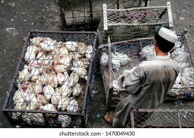 Landi Kotal, Khyber Pass, Khyber Pakhtunkhwa / Pakistan - Aug 16 2005: A Muslim man takes chickens to market in Landi Kotal, Pakistan. The chickens are in cages. Landi Kotal is on the Khyber Pass.