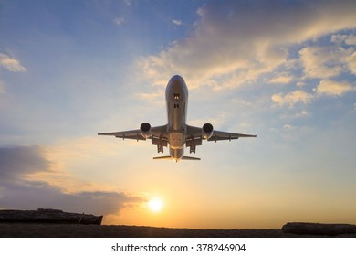 landing aircraft with sunset sky background