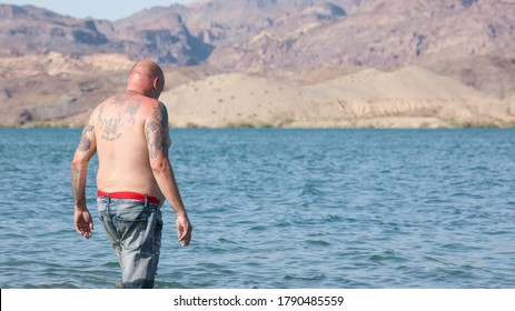 Nelson's Landing Cliff Jumping, Searchlight, NV 8/5/2020 — A bald middle aged Caucasian man with tattoos walks into the Colorado River in his jeans. Captured before sunset.