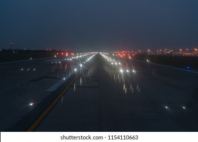Landing lights ON A airport runway at nighT sky.