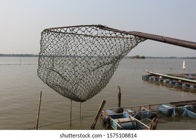 Landing Net with a long iron handle. There is a sky and the water in the lake as the backdrop, Fishing equipment for fishing people or inland fisheries in Phayao Lake, Northern Thailand.