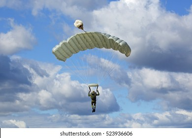 The landing - paratrooper fly in the background of the blue sky