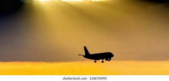 Landing passenger plane in airport at the dark evening time on  beautiful golden orange sunset background