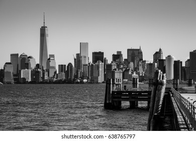 Landing pier at Liberty Island in front of New York skyline Black and White