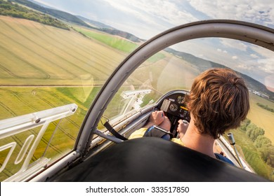 Landing of plane with pilot on natural airport, Pilot in cockpit of plane during landing, Flying small sailplane with pilot