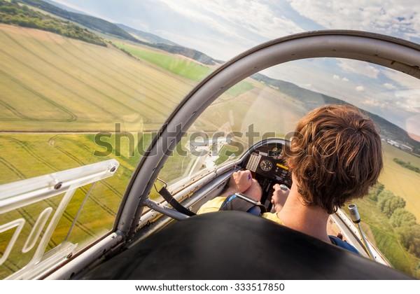 Landung des Flugzeugs mit Piloten auf dem natürlichen Flughafen, Piloten im Cockpit des Flugzeuges während der Landung, Flying Small Segelflugzeug mit Pilot