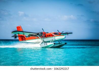 Landing seaplane in the ocean lagoon. The takeoff of a seaplane at ocean beach.