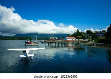 Landing a seaplane on the lake with pier and dock and mountains in the backgrounds, dramatic cloudy sky on a sunny summer day on Vancouver Island in British Columbia Canada