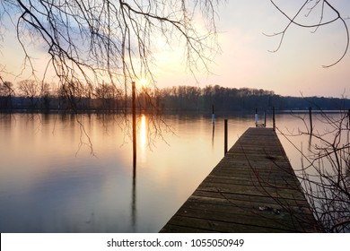 landing stage above glassy water at sunset