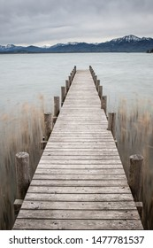 Landing stage with blurred water at the sea and mountains in the background with dramatic sky