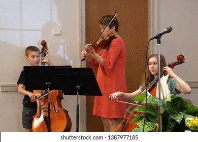 Landisville, PA, USA - April 21, 2019: a family plays a string quartet (bass, violin, cello and piano [not visible]) at church on a Sunday morniing