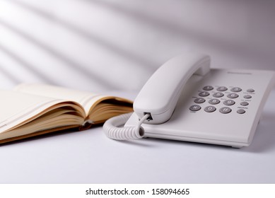 Landline dial up telephone and open note book or diary on a white table in sunlight with radiating shadows