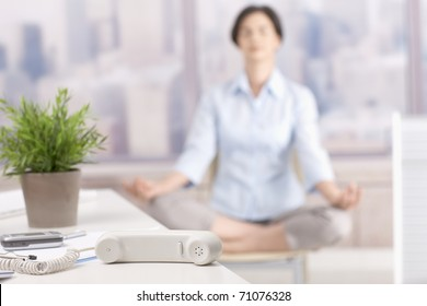 Landline phone put aside in skyscraper office, woman meditating in background.?