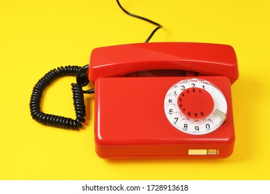 Landline red telephone on a yellow background.An old Soviet vintage telephone.